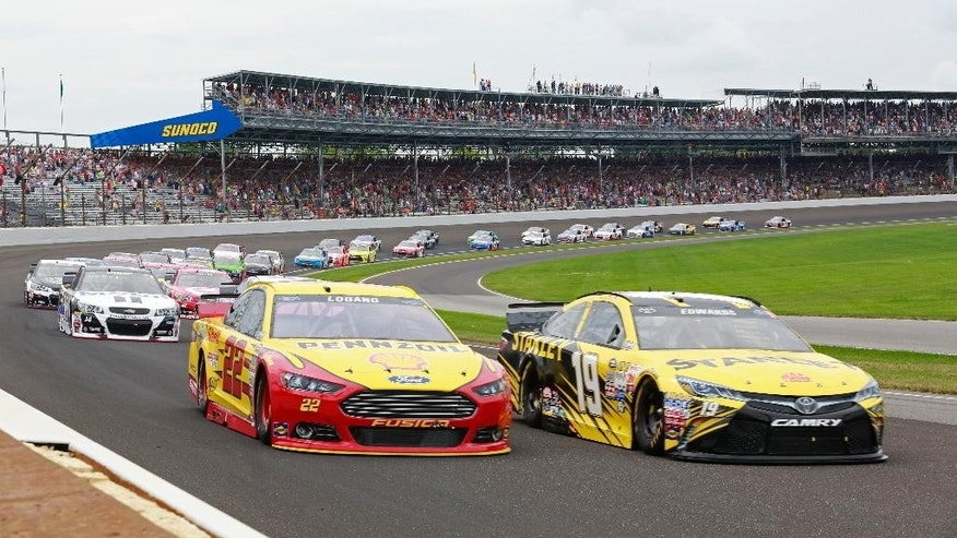 Carl Edwards and Joey Logano lead the field through the first turn on the start of the NASCAR Brickyard 400 auto race at Indianapolis Motor Speedway in Indianapolis
