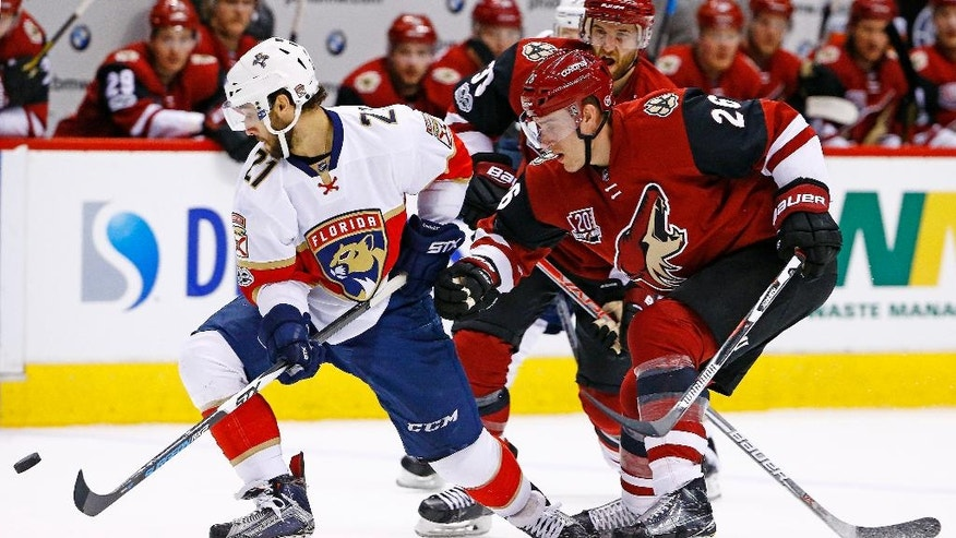Florida Panthers center Vincent Trocheck (21) battles with Arizona Coyotes defenseman Michael Stone (26) and defenseman Alex Goligoski (33) for the puck during the first period of an NHL hockey game, Monday, Jan. 23, 2017, in Glendale, Ariz. (AP Photo/Ross D. Franklin)