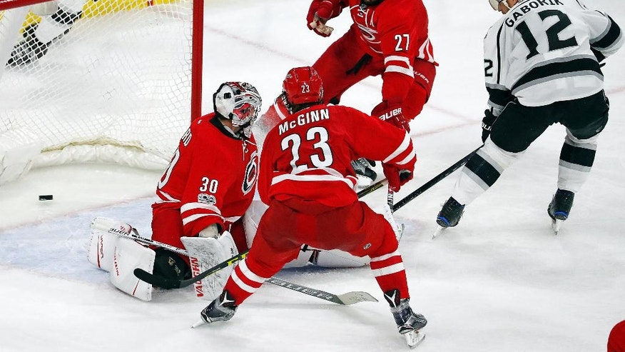Los Angeles Kings' Marian Gaborik (12) slips the puck through the defense of Carolina Hurricanes' Justin Faulk (27), Brock McGinn (23) and goalie Cam Ward (30) to score the go-ahead goal during the third period of an NHL hockey game, Thursday, Jan. 26, 2017, in Raleigh, N.C. (AP Photo/Karl B DeBlaker)