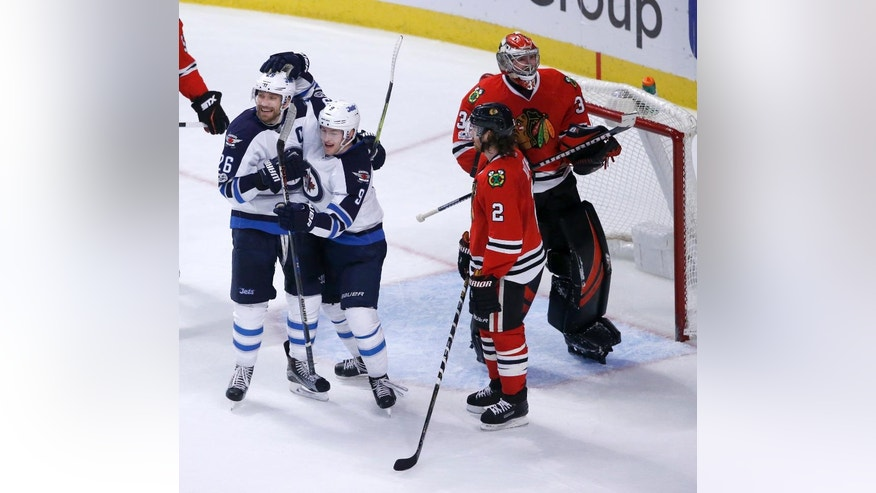 Winnipeg Jets' Andrew Copp (9) and Blake Wheeler (26) celebrate Copp's goal as Chicago Blackhawks' Duncan Keith (2) and Scott Darling (33) watch during the third period of an NHL hockey game Thursday, Jan. 26, 2017, in Chicago. The Jets won 5-3. (AP Photo/Charles Rex Arbogast)