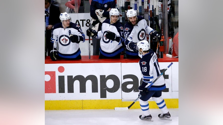 Winnipeg Jets' Bryan Little (18) celebrates his goal with teammates Mark Scheifele (55), Brandon Tanev and Chris Thorburn (22) during the third period of an NHL hockey game against the Chicago Blackhawks Thursday, Jan. 26, 2017, in Chicago. The Jets won 5-3. (AP Photo/Charles Rex Arbogast)