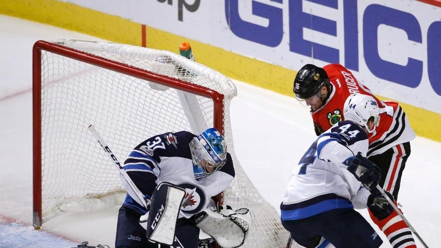 Winnipeg Jets goalie Connor Hellebuyck (37) makes a save on a shot by Chicago Blackhawks' Marcus Kruger, right, as Josh Morrissey (44) also defends during the second period of an NHL hockey game Thursday, Jan. 26, 2017, in Chicago. (AP Photo/Charles Rex Arbogast)