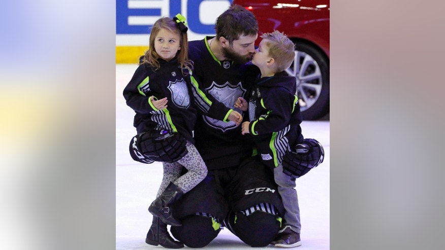 FILE - In this Jan. 25, 2015, file photo, Team Foligno's Brent Burns of the San Jose Sharks gets a kiss from his son after bringing his son and daughter onto the ice at the conclusion of the NHL All-Star hockey game in Columbus, Ohio. A five-day bye week for each team is a new wrinkle added to the NHL this season so players can get a breather during the second half of a grueling, 82-game grind. Mike Smith felt weird that other teams were playing while he and the Arizona Coyotes were off and relaxing, but that didn't deter the All-Star goaltender from going sledding with his kids and taking advantage of the downtime. (AP Photo/Gene J. Puskar, File)