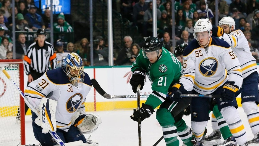 Buffalo Sabres' Anders Nilsson (31) defends against a shot from the Dallas Stars as Antoine Roussel (21) pressures the net during the first period of an NHL hockey game, Thursday, Jan. 26, 2017, in Dallas. Sabres' Rasmus Ristolainen helps defend on the play. (AP Photo/Tony Gutierrez)