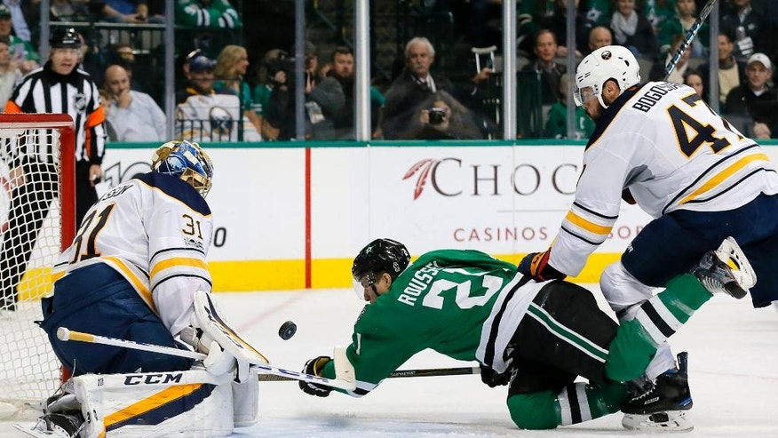Dallas Stars left wing Antoine Roussel (21) attempts a shot from the ice as Buffalo Sabres' Anders Nilsson (31) and Zach Bogosian (47) defend the net during the first period of an NHL hockey game, Thursday, Jan. 26, 2017, in Dallas. (AP Photo/Tony Gutierrez)