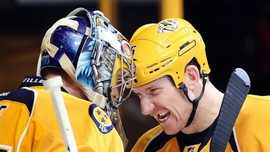 Nashville Predators left wing Cody McLeod, right, bumps helmets with goalie Pekka Rinne, of Finland, as they celebrate the team's 4-3 win over the Columbus Blue Jackets in an NHL hockey game Thursday, Jan. 26, 2017, in Nashville, Tenn. (AP Photo/Mark Humphrey)
