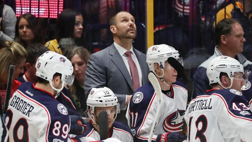 Columbus Blue Jackets assistant coach Brad Larsen, center, looks at the scoreboard during the third period of the team's NHL hockey game against the Nashville Predators on Thursday, Jan. 26, 2017, in Nashville, Tenn. Three assistant coaches were behind the bench as Blue Jackets coach John Tortorella returned to Ohio because of a family emergency, keeping him out of both the game with the Predators and the NHL All-Star Game this weekend. The Predators won 4-3. (AP Photo/Mark Humphrey)