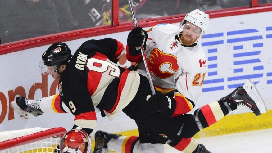 Calgary Flames defenseman Dougie Hamilton (27) and Ottawa Senators right wing Bobby Ryan (9) get tangled up during the third period of an NHL hockey game Thursday, Jan. 26, 2017, in Ottawa, Ontario. (Sean Kilpatrick/The Canadian Press via AP)