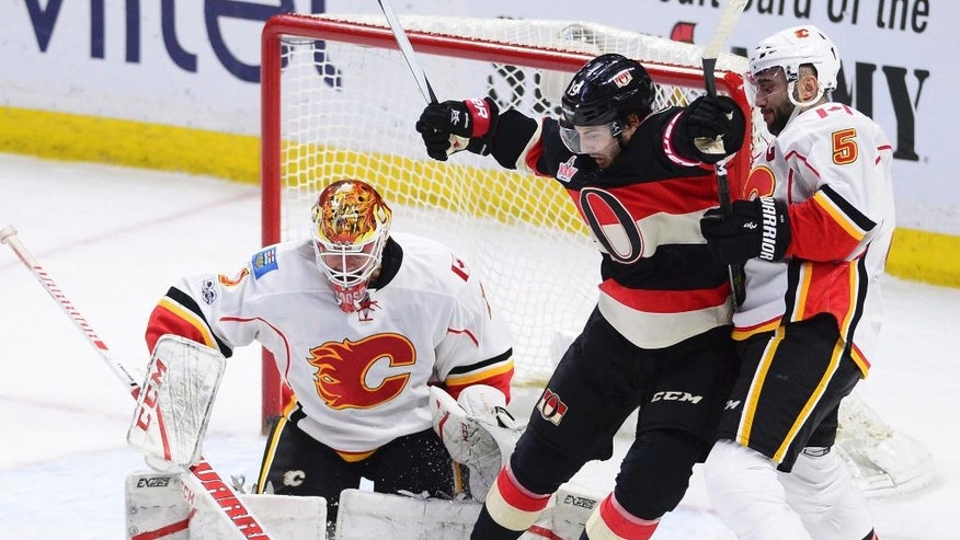 Ottawa Senators center Derick Brassard (19) attempts to avoid a shot as he blocks Calgary Flames defenseman Mark Giordano (5) in front of goalie Brian Elliott (1) during the second period of an NHL hockey game Thursday, Jan. 26, 2017, in Ottawa, Ontario. (Sean Kilpatrick/The Canadian Press via AP)