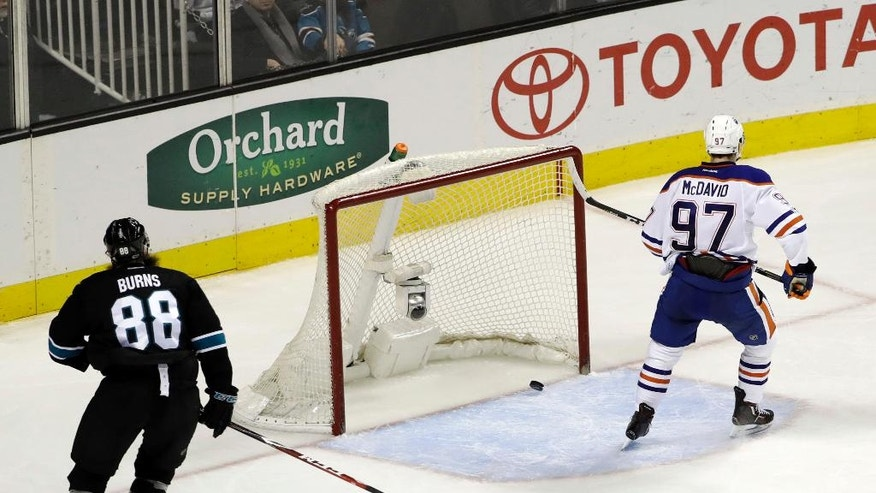 Edmonton Oilers' Connor McDavid (97) scores an empty-net goal past San Jose Sharks' Brent Burns (88) during the third period of an NHL hockey game Thursday, Jan. 26, 2017, in San Jose, Calif. Edmonton won 4-1. (AP Photo/Marcio Jose Sanchez)