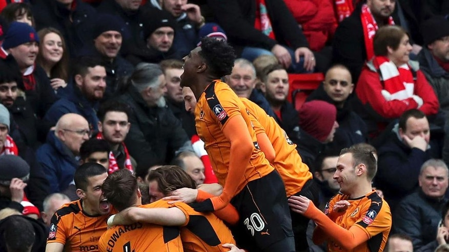 Wolverhampton Wanderers' Richard Stearman, celebrates scoring his side's first goal of the game with his teammates during the FA Cup, fourth round soccer match between Liverpool and Wolverhampton Wanderers, at Anfield, in Liverpool, England, Saturday,  Jan.  28, 2017. (Peter Byrne/PA via AP)