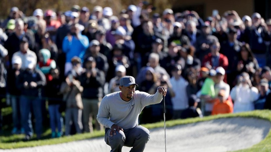 Tiger Woods looks over his ball on the 18th hole of the North Course during the second round of the Farmers Insurance Open golf tournament Friday, Jan. 27, 2017, at Torrey Pines Golf Course in San Diego. (AP Photo/Gregory Bull)