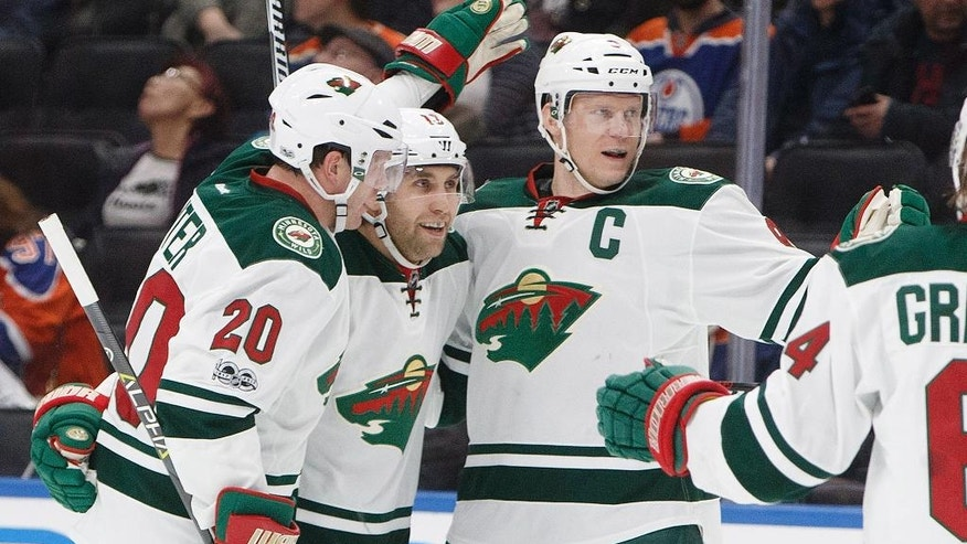 Minnesota Wild defenseman Ryan Suter (20), left wing Jason Zucker (16) and centre Mikko Koivu (9) celebrate a goal against the Edmonton Oilers during the first period of an NHL hockey game Tuesday, Jan. 31, 2017, in Edmonton, Alberta. (Jason Franson/The Canadian Press via AP)