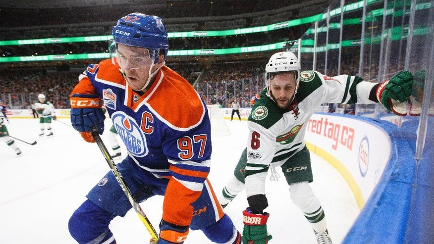 Minnesota Wild defenaeman Marco Scandella (6) and Edmonton Oilers center Connor McDavid (97) compete in the corner during the second period of an NHL hockey game Tuesday, Jan. 31, 2017, in Edmonton, Alberta. (Jason Franson/The Canadian Press via AP)