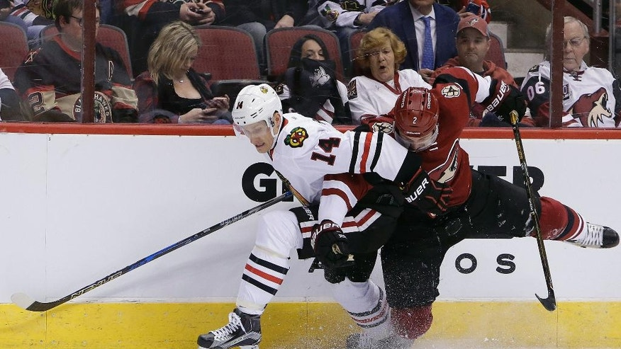 Chicago Blackhawks left wing Richard Panik (14) shields Arizona Coyotes defenseman Luke Schenn from the puck in the first period during an NHL hockey game, Thursday, Feb. 2, 2017, in Glendale, Ariz. (AP Photo/Rick Scuteri)