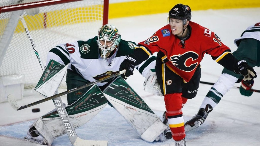 Minnesota Wild goalie Devan Dubnyk watches as Calgary Flames left wing Matthew Tkachuk (19) tries to deflect a shot into the net during the first period of an NHL hockey game Wednesday, Feb. 1, 2017, in Calgary, Alberta. (Jeff McIntosh/The Canadian Press via AP)