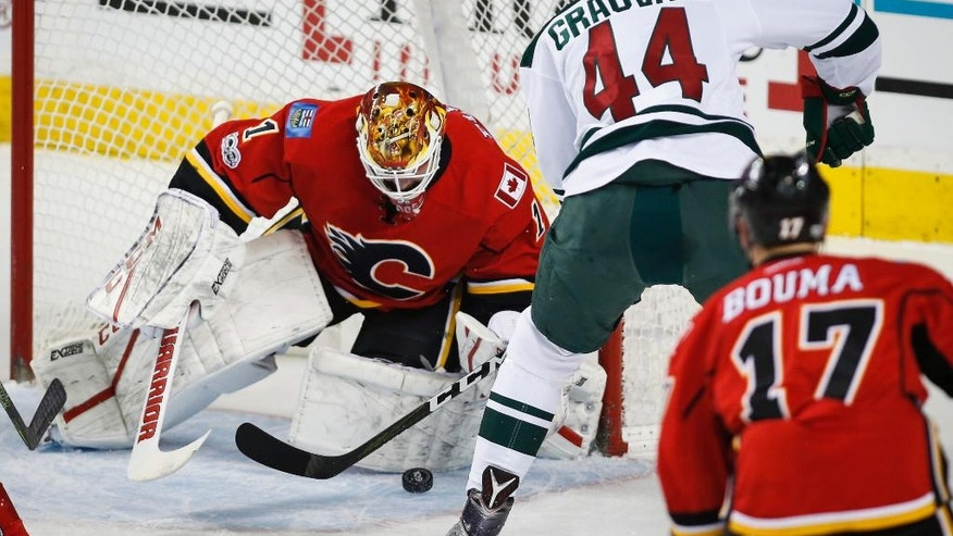 Minnesota Wild center Tyler Graovac (44) tries to get the puck past Calgary Flames goalie Brian Elliott (1) during the first period of an NHL hockey game Wednesday, Feb. 1, 2017, in Calgary, Alberta. (Jeff McIntosh/The Canadian Press via AP)