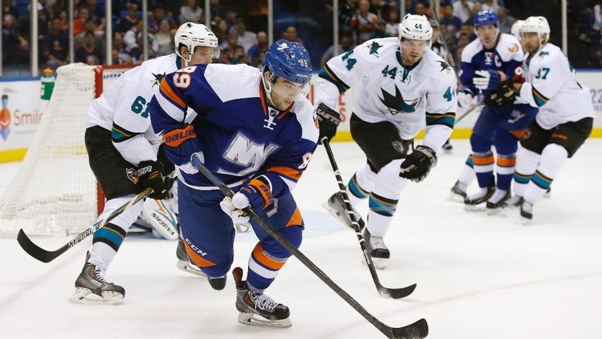 FILE - In this Oct. 16, 2014, file photo, New York Islanders left wing Cory Conacher (89) moves the puck away from San Jose Sharks defensemen Justin Braun (61) and Marc-Edouard Vlasic (44) during the second period of an NHL hockey game in Uniondale, N.Y. Conacher, only four years removed from being a Calder Trophy candidate as NHL rookie of the year, has been in four different organizations and spent time in Europe since then. He sees the sport getting younger and faster and more players his age getting squeezed out. (AP Photo/Kathy Willens, File)