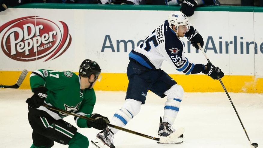 Winnipeg Jets center Mark Scheifele (55) skates the puck past Dallas Stars center Devin Shore (17) during the third period of an NHL hockey game, Thursday, Feb. 2, 2017, in Dallas. The Jets won 4-3. (AP Photo/Jim Cowsert)