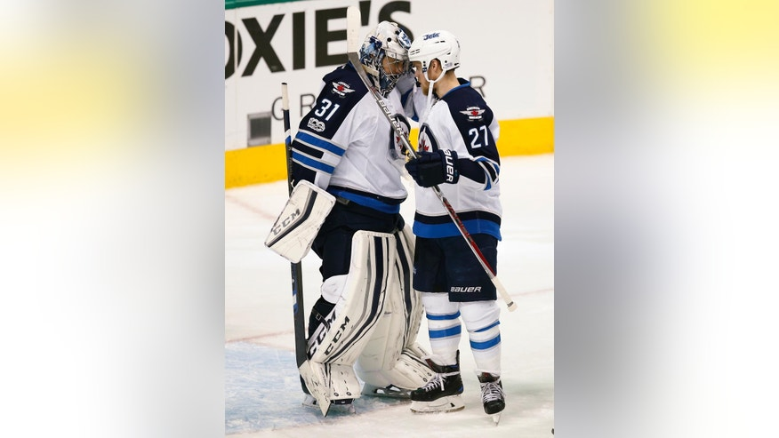 Winnipeg Jets goalie Ondrej Pavelec (31) and left wing Nikolaj Ehlers (27) celebrate the team's 4-3 win over win over the Dallas Stars in an NHL hockey game, Thursday, Feb. 2, 2017, in Dallas. (AP Photo/Jim Cowsert)