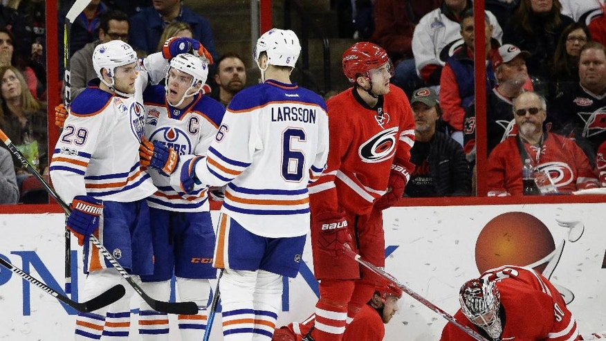 Edmonton Oilers' Connor McDavid, center of group at left, is congratulated by Leon Draisaitl (29), of Germany, and Adam Larsson (6), of Sweden, following McDavid's goal against Carolina Hurricanes goalie Cam Ward, right, as Hurricanes Noah Hanifin (5) skates away during the second period of an NHL hockey game in Raleigh, N.C., Friday, Feb. 3, 2017. (AP Photo/Gerry Broome)