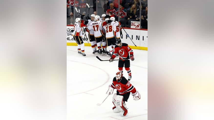 Calgary Flames players, top, celebrate a game-winning goal in by Mikael Backlund, of Sweden, as New Jersey Devils goalie Cory Schneider (35) and defenseman Damon Severson (28) skate off the ice during overtime of an NHL hockey game, Friday, Feb. 3, 2017, in Newark, N.J. The Flames won 4-3 in overtime. (AP Photo/Julio Cortez)