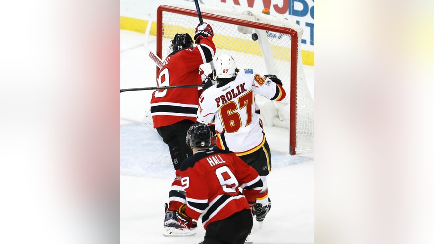 A shot by Calgary Flames center Mikael Backlund, not pictured, of Sweden, is seen in the net after scoring the game-wining goal against the New Jersey Devils during overtime of an NHL hockey game, Friday, Feb. 3, 2017, in Newark, N.J. The Flames won 4-3 in overtime. (AP Photo/Julio Cortez)