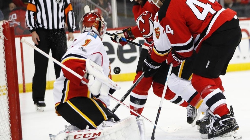 The puck bounces off New Jersey Devils right wing Kyle Palmieri, center, before entering the net of Calgary Flames goalie Brian Elliott (1) for a goal during the second period of an NHL hockey game, Friday, Feb. 3, 2017, in Newark, N.J. Devils' Miles Wood (44) and Flames' Mark Giordano (5) are seen on play. (AP Photo/Julio Cortez)