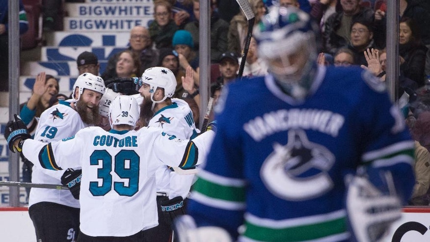 San Jose Sharks left wing Patrick Marleau (12) celebrates his goal with teammates Joe Thornton (19) and Logan Couture (39) as Vancouver Canucks goalie Ryan Miller (30) looks on during first-period NHL hockey game action in Vancouver, British Columbia, Thursday, Feb. 2, 2017. (Jonathan Hayward/The Canadian Press via AP)