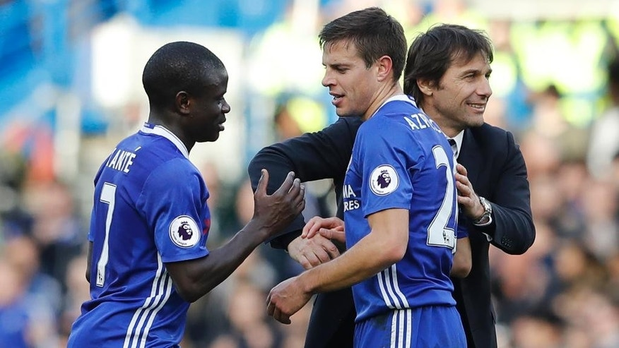 Chelsea's manager Antonio Conte pats the back of Chelsea's Cesar Azpilicueta who shakes hands with teammate Chelsea's N'Golo Kante after the end of the English Premier League soccer match between Chelsea and Arsenal at Stamford Bridge stadium in London, Saturday, Feb. 4, 2017. Chelsea won the game 3-1. (AP Photo/Frank Augstein)