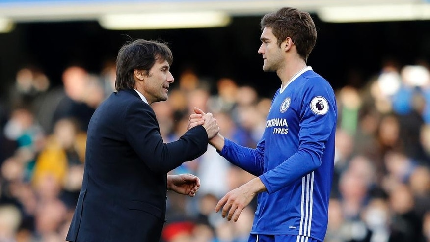 Chelsea's manager Antonio Conte, left shakes hands with his player Chelsea's Marcos Alonso after the end of the English Premier League soccer match between Chelsea and Arsenal at Stamford Bridge stadium in London, Saturday, Feb. 4, 2017. Chelsea won the match 3-1. (AP Photo/Frank Augstein)