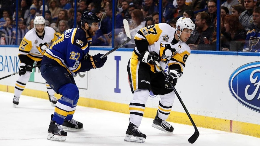 Pittsburgh Penguins' Sidney Crosby, right, passes the puck as teammate Bryan Rust, left rear, and St. Louis Blues' Alex Pietrangelo watch during the first period of an NHL hockey game Saturday, Feb. 4, 2017, in St. Louis. (AP Photo/Jeff Roberson)