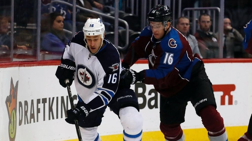 Winnipeg Jets left wing Shawn Matthias, left, picks up a loose puck as Colorado Avalanche defenseman Nikita Zadorov, of Russia, defends in the second period of an NHL hockey game Saturday, Feb. 4, 2017, in Denver. (AP Photo/David Zalubowski)
