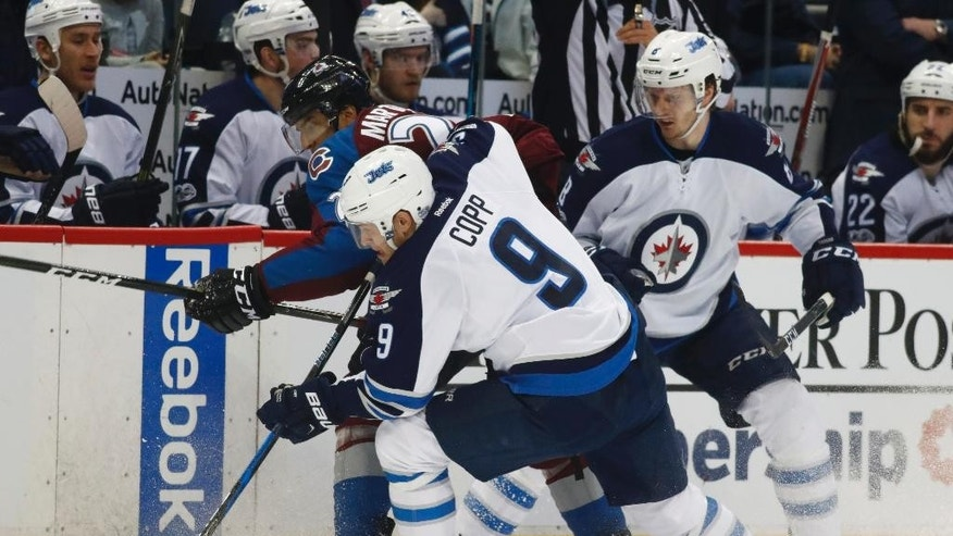 Winnipeg Jets center Andrew Copp (9), front, clears the puck from the boards as Colorado Avalanche left wing Andreas Martinsen, back left, of Norway, and Jets defenseman Jacob Trouba look on in the second period of an NHL hockey game Saturday, Feb. 4, 2017, in Denver. (AP Photo/David Zalubowski)