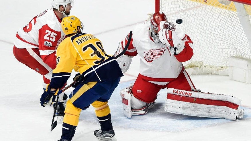 Detroit Red Wings goalie Petr Mrazek (34), of the Czech Republic, deflects a shot by Nashville Predators left wing Viktor Arvidsson (38), of Sweden, during the first period of an NHL hockey game Saturday, Feb. 4, 2017, in Nashville, Tenn. (AP Photo/Mark Zaleski)