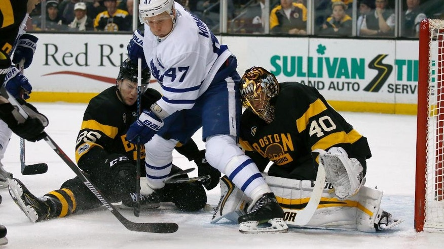 Boston Bruins goalie Tuukka Rask (40) and defenseman Brandon Carlo (25) look to clear the puck as Toronto Maple Leafs center Leo Komarov (47) looks for a rebound during the first period of an NHL hockey game in Boston, Saturday, Feb. 4, 2017. (AP Photo/Mary Schwalm)