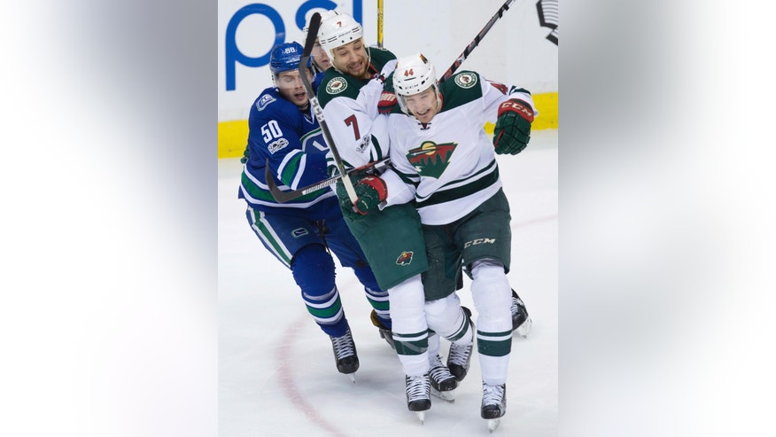 Vancouver Canucks' Brendan Gaunce (50) and Minnesota Wild's Chris Stewart (7), Tyler Graovac (44) and Charlie Coyle, back, collide during the third period of an NHL hockey game Saturday, Feb. 4, 2017, in Vancouver, British Columbia. (Darry Dyck/The Canadian Press via AP)