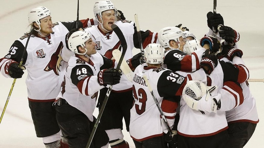 Arizona Coyotes goalie Mike Smith, right, is congratulated by teammates after the Coyotes beat the San Jose Sharks in an NHL hockey game in San Jose, Calif., Saturday, Feb. 4, 2017. The Coyotes won in shootout, 3-2. (AP Photo/Jeff Chiu)