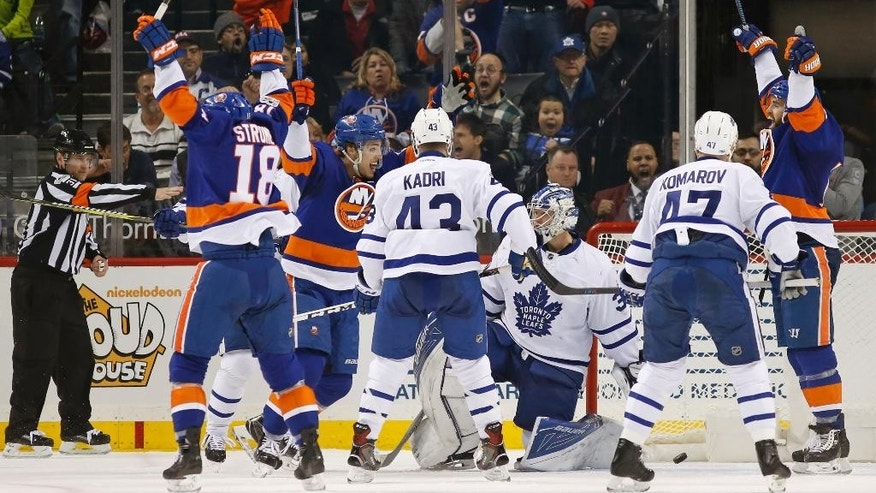 New York Islanders left wing Andrew Ladd, far right, celebrates his game-tying goal on Toronto Maple Leafs goalie Frederik Andersen, of Denmark, third from right, during the third period of an NHL hockey game in New York, Monday, Feb. 6, 2017. The Islanders defeated the Maple Leafs 6-5. (AP Photo/Kathy Willens)