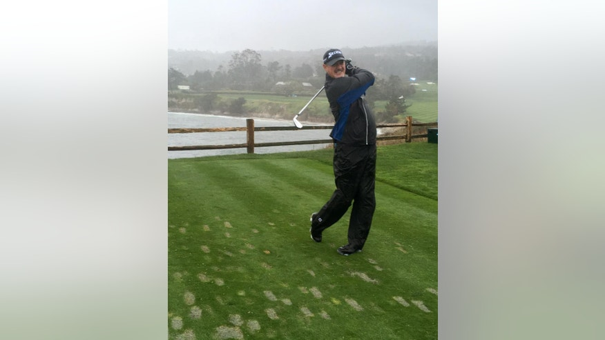 PGA Tour veteran Jerry Kelly tees off with a 4-iron into the wind on the 106-yard seventh hole at Pebble beach, Calif., on Tuesday, Feb. 7, 2017. Even in conditions so bad Tuesday that the course was closed to spectators, Kelly couldn't wait to play with Green Bay quarterback Aaron Rodgers and two friends.  (AP Photo/Doug Ferguson)