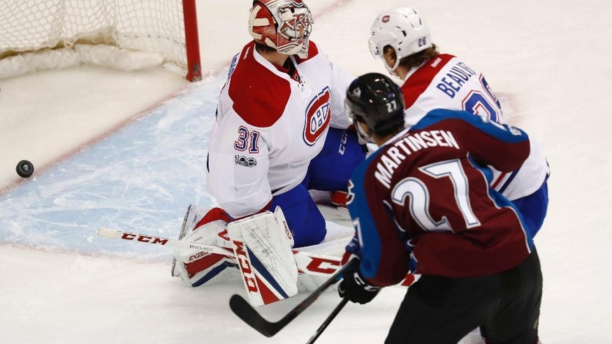 Colorado Avalanche left wing Andreas Martinsen, front, of Norway, watches as his shot dribbles in for a goal past Montreal Canadiens defenseman Nathan Beaulieu, back right, and goalie Carey Price during the first period of an NHL hockey game Tuesday, Feb. 7, 2017, in Denver. (AP Photo/David Zalubowski)