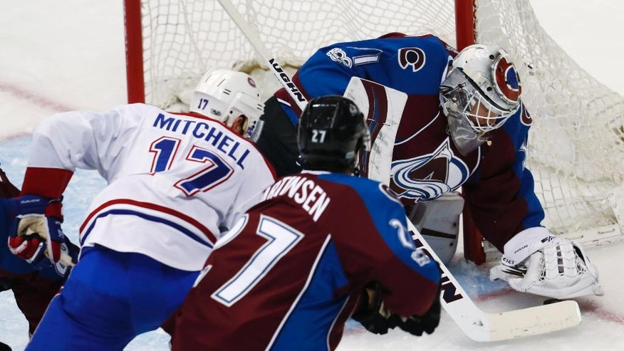 Colorado Avalanche goalie Calvin Pickard, back, covers the puck after stopping a shot by Montreal Canadiens center Torrey Mitchell, front left, as Avalanche left wing Andreas Martinsen, of Norway, defends during the first period of an NHL hockey game Tuesday, Feb. 7, 2017, in Denver. (AP Photo/David Zalubowski)