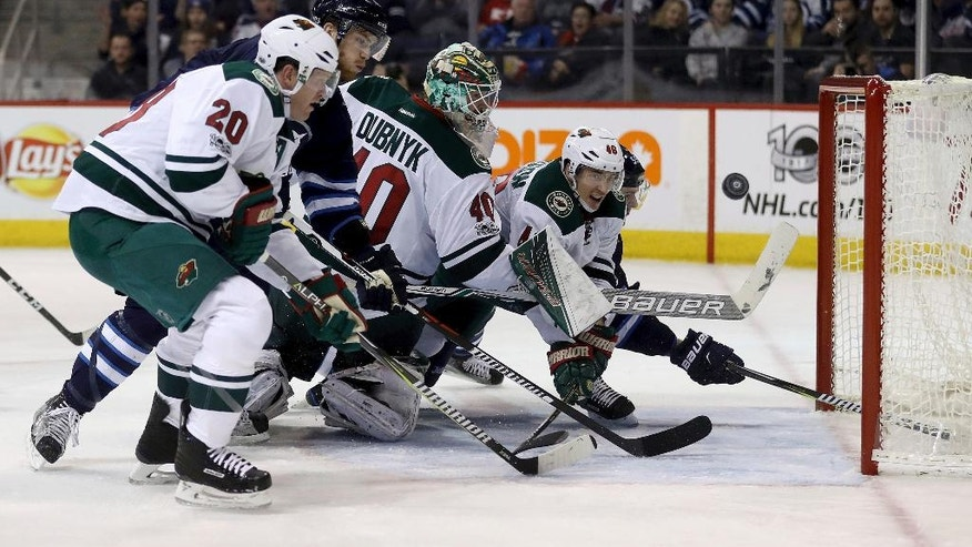 Minnesota Wild defenseman Jared Spurgeon (46) swipes the puck out from behind goaltender Devan Dubnyk (40) with defenseman Ryan Suter (20) and Winnipeg Jets Adam Lowry (17) and centre Mark Scheifele (55) in front of the net during the second period of an NHL hockey game Tuesday, Feb. 7, 2017, in Winnipeg, Manitoba. (Trevor Hagan/The Canadian Press via AP)