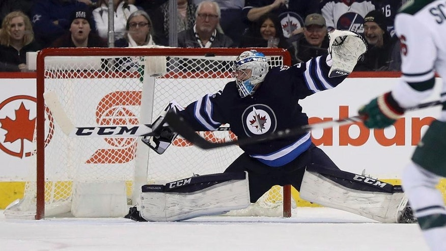 Winnipeg Jets goalie Connor Hellebuyck (37) stretches to make a save as the puck hits the crossbar on a shot by the Minnesota Wild during the second period of an NHL hockey game Tuesday, Feb. 7, 2017, in Winnipeg, Manitoba. (Trevor Hagan/The Canadian Press via AP)