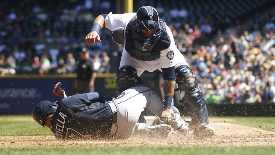 Aug 6, 2014; Seattle, WA, USA; Seattle Mariners catcher Jesus Sucre (2) blocks Atlanta Braves second baseman Tommy La Stella (7) from scoring a run during the third inning at Safeco Field. Mandatory Credit: Joe Nicholson-USA TODAY Sports