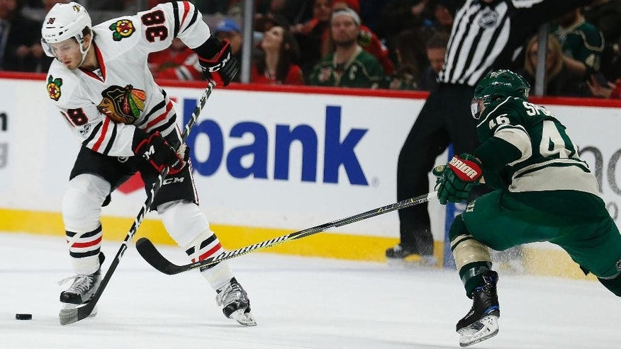 Chicago Blackhawks' Ryan Hartman (38) controls the puck against Minnesota Wild's Jared Spurgeon (46) in the second period of an NHL hockey game, Wednesday, Feb. 8, 2017, in St. Paul, Minn. (AP Photo/Stacy Bengs)