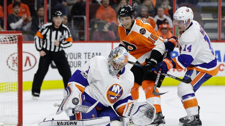 New York Islanders' Thomas Greiss (1) blocks a shot as Philadelphia Flyers' Brayden Schenn (10) and Thomas Hickey (14) look for the rebound during the second period of an NHL hockey game, Thursday, Feb. 9, 2017, in Philadelphia. (AP Photo/Matt Slocum)