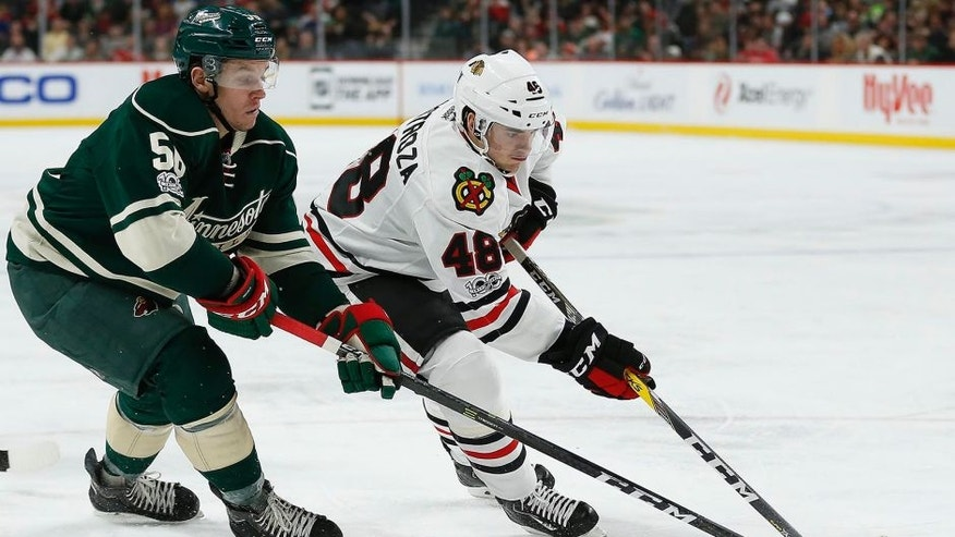 Chicago Blackhawks' Vinnie Hinostroza (48) controls the puck against Minnesota Wild's Erik Haula (56) in the second period of an NHL hockey game, Wednesday, Feb. 8, 2017, in St. Paul, Minn. (AP Photo/Stacy Bengs)