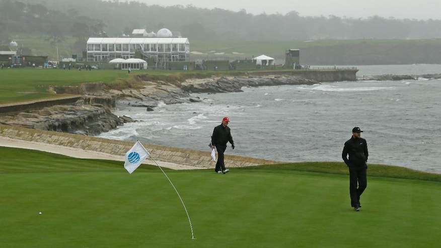 Kevin Tway, right, walks in the wind and rain up to the 18th green of the Pebble Beach Golf Links during the first round of the AT&T Pebble Beach National Pro-Am golf tournament Thursday, Feb. 9, 2017, in Pebble Beach, Calif. (AP Photo/Eric Risberg)