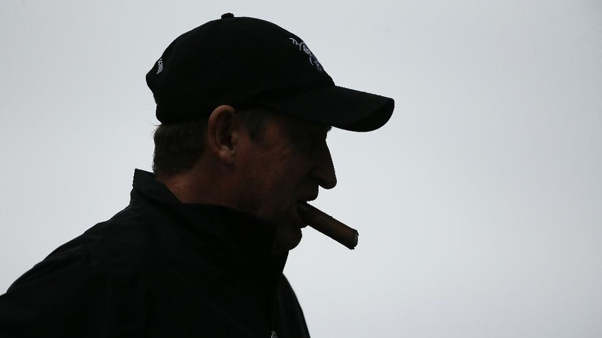 Wayne Gretzky smokes a cigar while waiting to hit from the fourth tee of the Monterey Peninsula Country Club Shore Course during the first round of the AT&T Pebble Beach National Pro-Am golf tournament Thursday, Feb. 9, 2017, in Pebble Beach, Calif. (AP Photo/Eric Risberg)